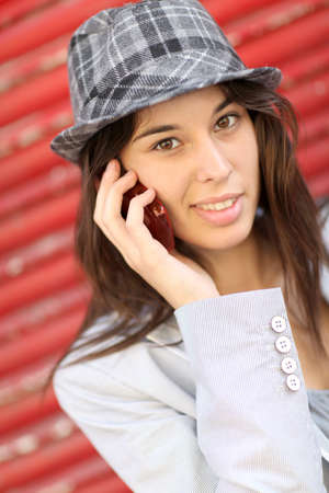 trendy girl: Portrait of trendy girl leaning on red background Stock Photo