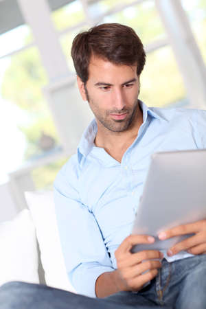 handsom: Guy Handsom usando tableta electr�nica en el hogar