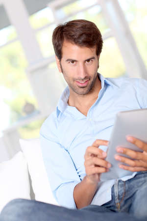 Handsom guy using electronic tablet at home photo