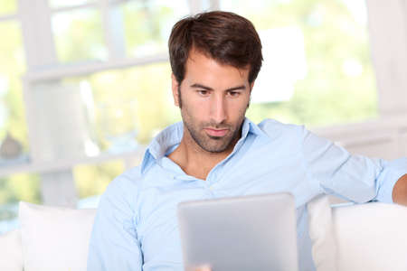 Handsom guy using electronic tablet at home Stock Photo - 10797982