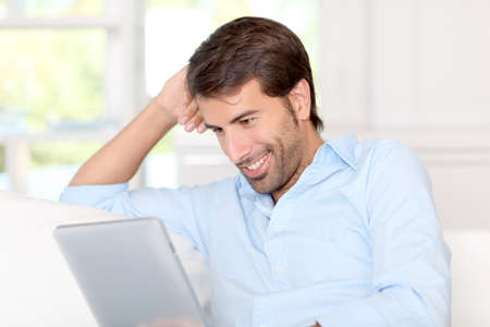 Handsom guy using electronic tablet at home Stock Photo - 10797875