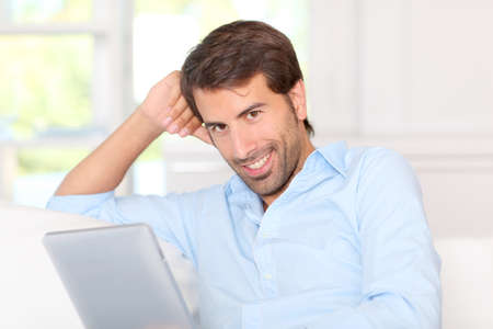 Handsom guy using electronic tablet at home Stock Photo - 10797874