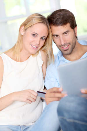 secured payment: Young couple at home doing online shopping