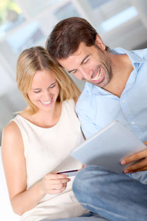 Young couple at home doing online shopping photo