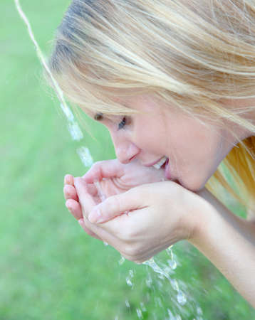Young woman drinking water from fountain Stock Photo