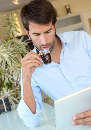 hombre tomando cafe: Hombre el consumo de caf� durante el uso de tabletas