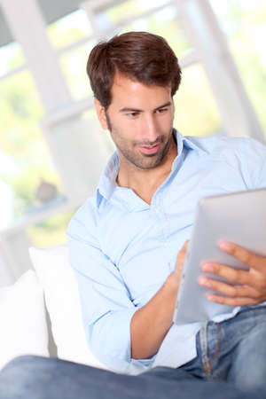Handsom guy using electronic tablet at home Stock Photo - 10803433