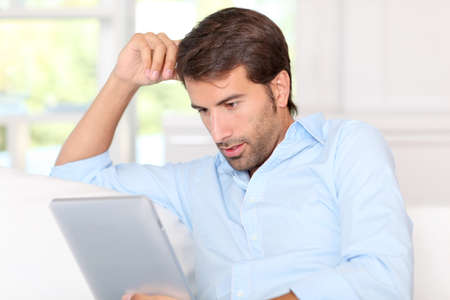 Handsom guy using electronic tablet at home Stock Photo - 10803432