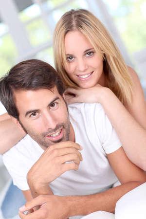man woman hugging: Young couple laying down sofa
