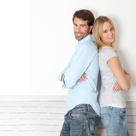 Young couple standing on white wall photo