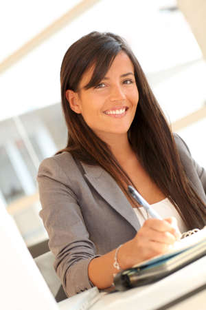 Portrait of beautiful businesswoman writing notes on agenda Stock Photo - 10978932
