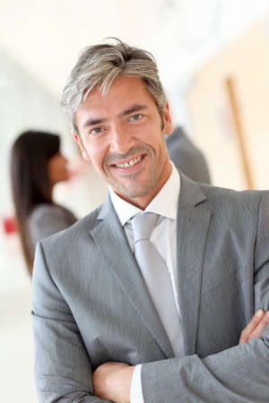 Portrait of handsome businessman standing in hall photo