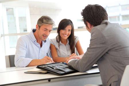 firmando: Padre y el adolescente la firma del contrato de préstamo