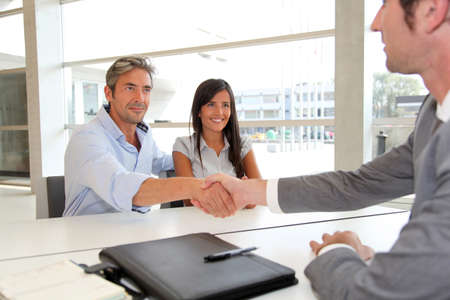 adviser: Man giving handshake to real-estate-agent Stock Photo