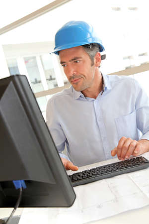 Engineer in office working on construction plan photo