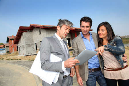 property investment: Real-estate agent showing house under construction to couple