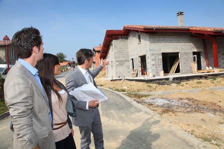 Real-estate agent showing plan to young home investors photo