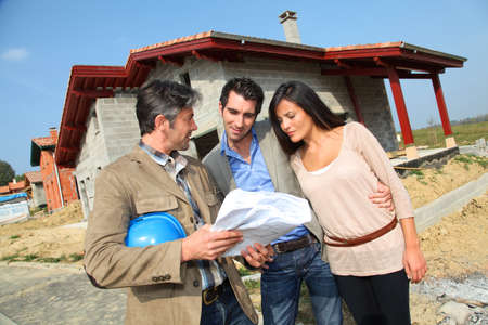 Entrepreneur showing house under construction to couple Stock Photo - 10979178