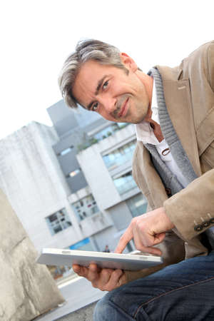 Handsome guy in town using electronic tablet Stock Photo - 10979111