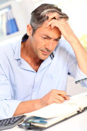 Man in office with worried look on his face photo