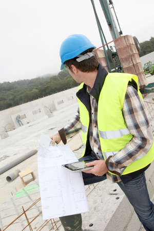 building site: Construction manager using electronic tablet on site Stock Photo
