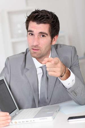 Businessman showing something on laptop computer Stock Photo - 10978883