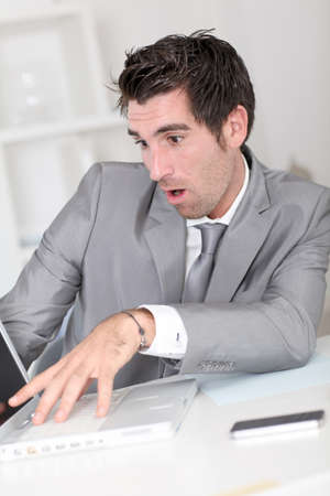 shoked: Surprised businessman looking at laptop computer