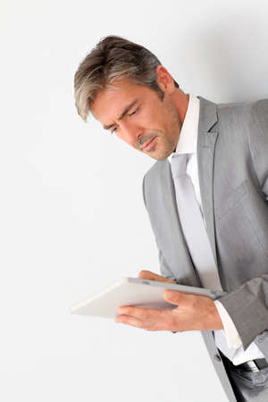 40 years old man: Businessman standing on grey background with touchpad