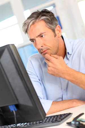 worried man: Man working in office with worried look Stock Photo