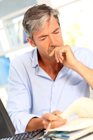 worried man: Man in office with worried look on his face