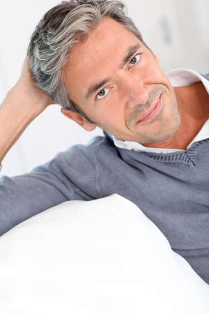 gray hair: Handsome man relaxing in sofa at home