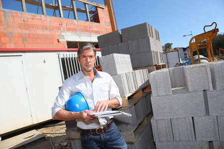 construction plans: Entrepreneur checking plan on construction site