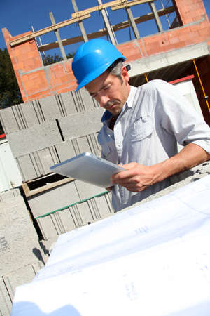 building site: Construction manager using electronic tablet on building site