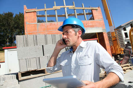 Engineer with blue security helmet talking on mobile phone photo
