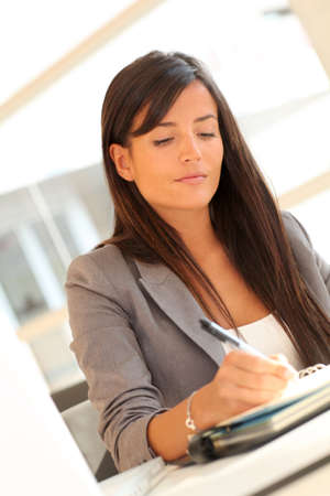 Portrait of beautiful businesswoman writing notes on agenda photo