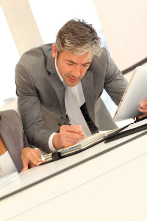 40 years old man: Businessman writing notes on agenda