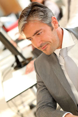 40 years old man: Handsome executive sitting at desk in office