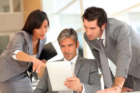reuniones empresariales: Reuni�n de negocios con la tableta electr�nica Foto de archivo