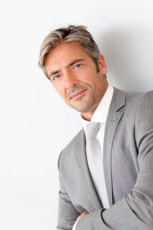 Portrait of handsome businessman standing on grey background photo