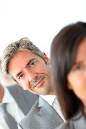 amongst: Smiling businessman standing amongst group Stock Photo