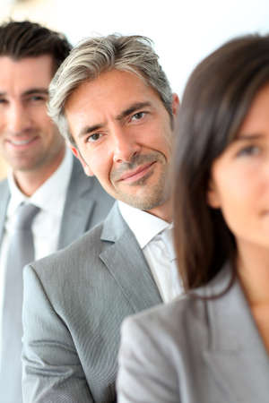40 years old man: Smiling businessman standing amongst group Stock Photo
