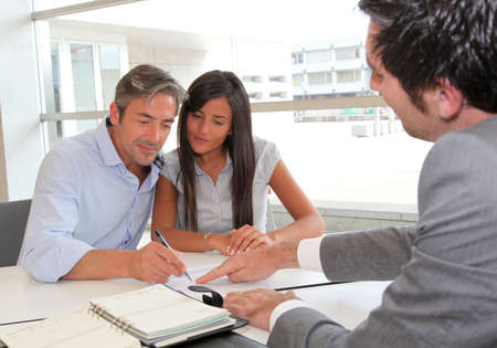 banker: Father and girl signing loan contract Stock Photo