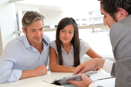 bankers: Real-estate agent showing house plans on electronic tablet Stock Photo