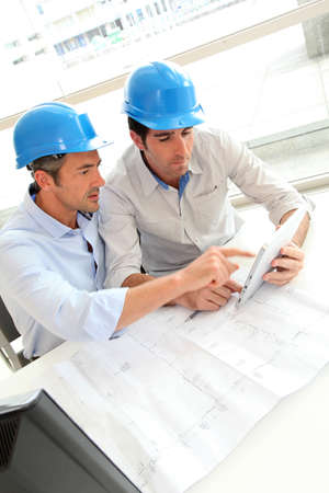 construction workers: Architects working on construction plan