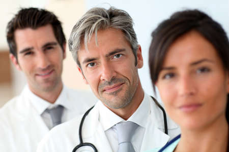 Portrait of doctor standing amongst medical team Stock Photo - 10979252