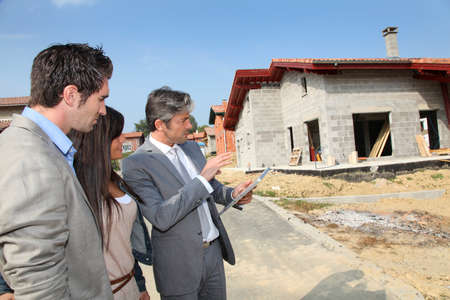 house under construction: Real-estate agent showing house under construction to couple