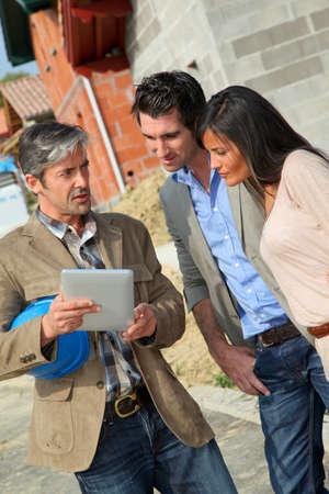 Entrepreneur showing house under construction to couple photo