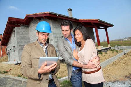 house under construction: Entrepreneur showing house under construction to couple