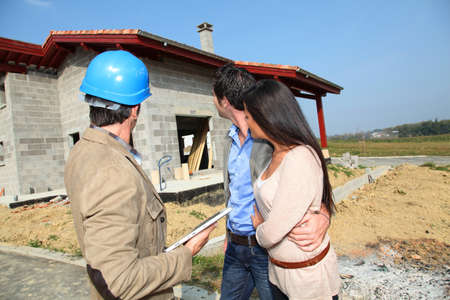 project property: Entrepreneur showing house under construction to couple