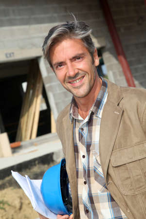 foremen: Portrait of smiling entrepreneur standing on construction site